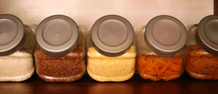various gluten-free cereals and pasta are in glass containers with gray plastic lids on a brown shelf as a fragment of the kitchen interior