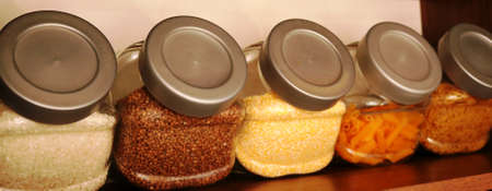 glass containers with plastic lids standing on a kitchen cabinet shelf and filled with textured free-flowing cereals and pasta from an angle of view, detail of the interior of home cooking