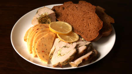 sliced turkey meatloaf, cheese interspersed with herbs and spices, two slices of rye bread and a couple of slices of lemon on a white plate on a dark brown background, serving a poultry appetizer