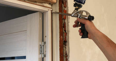 airtight fastening of the door frame with foam from a construction gun in the hands of the installer, the process of installing interior doors during major repairs