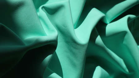 bright rich emerald material with a dense texture, shaded folds of pleated fabric with smooth curves, a shining mint-colored curved canvas