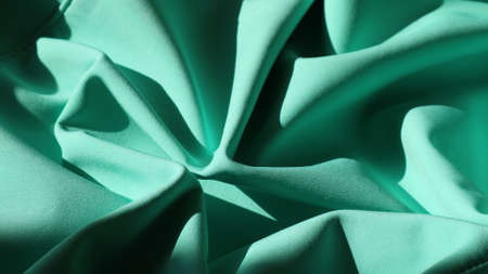 a dynamic art object made of dense emerald-colored fabric folded in the form of a flower bud, illuminated by bright light and shaded in places of bends, smooth lines of wavy mint-colored material Stock fotó