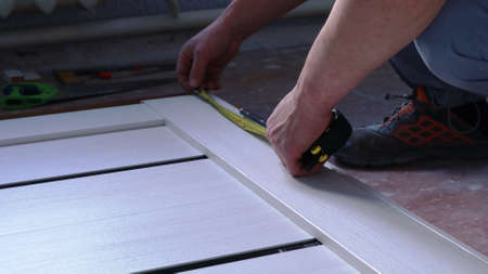 taking measurements on a light wooden canvas lying on the floor when installing metal fasteners using a tape measure in the hands of a carpenter, assembling a door frame on the floor in a room Stock Photo