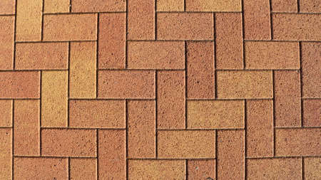 sandy brown natural stone in machined rectangular blocks laid out in pavement masonry, graphic resource of masonry in bright sunny detailed lighting view from the top angle full frame