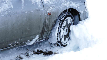 an icy dirty gray car caught in a snow trap, a car driven into a snowdrift on a snow-covered road after heavy snowfalls, extreme climatic conditions and consequences in everyday life