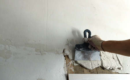 applying an elastic mortar to the wall in the process of leveling the surface after installing the door, the worker plastering the wall above the doorway