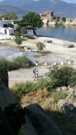 thee: Two tourists walking to the seaside in Bafa Golu, Turkey. Old Byzantine fortress on background.