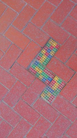 tile: Red ceramic tile on the road repaired by colorful toy blocks Stock Photo