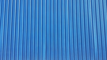 metal: Texture of blue metal siding with narrow vertical lines on the facade