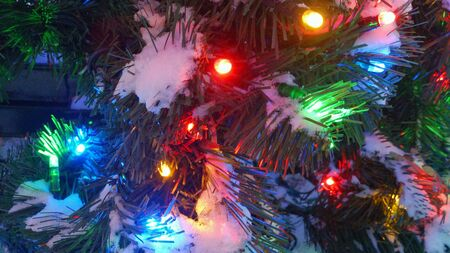 closeup: Texture of Illuminated Christmas tree fragment outdoor with snow close-up Stock Photo