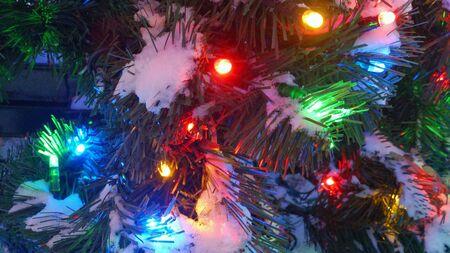 closeup: Texture of Illuminated Christmas tree fragment outdoor with snow close-up Stock Photo