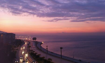 bright: Bright pink sunset in Izmir, Turkey. Horizontal landscape with sea and traffic on a road