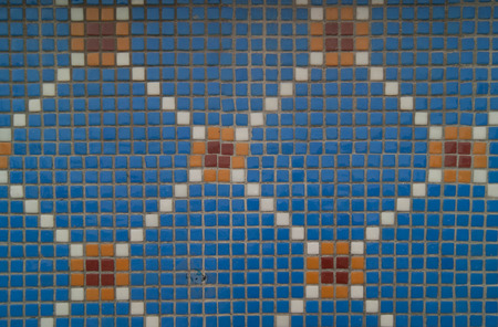 konya: Old blue mosaic with square pattern made of blue, white and orange tiles, placed on outdoor wall of old building in Konya, Turkey. Stock Photo