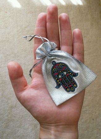 silver: Bag with hamsa symbol in girls hand