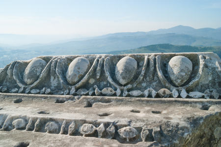 ionic: Part of old column with ionic ornament in the ancient Greek city of Pergamon with beautiful mountains on background
