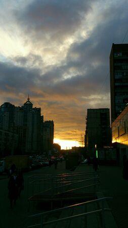 bright: Bright sunset and city silhouettes under cloudy sky