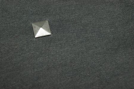heavy effect: Grey textile with metal stud close-up