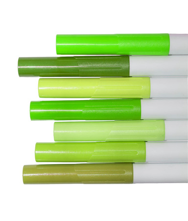 Markers in green tones close-up isolated on white background photo