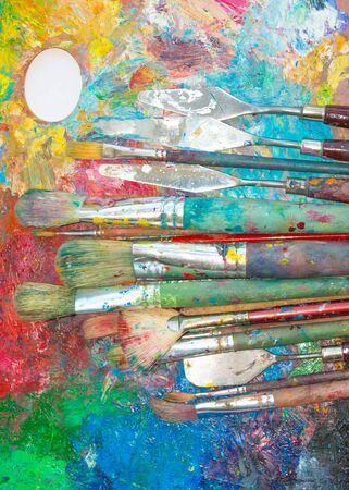 palette knife: Palette with oil paints and many big and small brushes and palette knife on it close-up