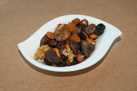 hardboard: dried figs, dried apricots, raisins, prunes, hazelnuts, almonds, walnuts in a white curly plate close-up on the background of hardboard with shadow
