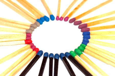 Matches with colored heads lie in a circle close-up isolated an white background