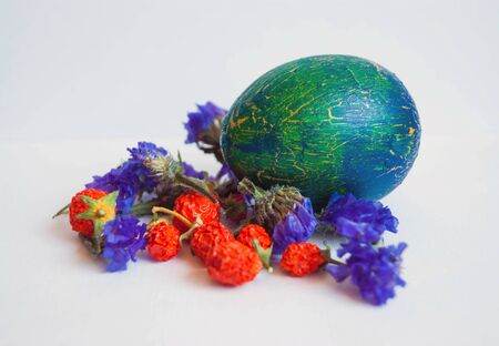 crackles: Small Solanum dried fruits, dried flowers Limonium and blue and green Easter egg decorated cracelures close-up on white background