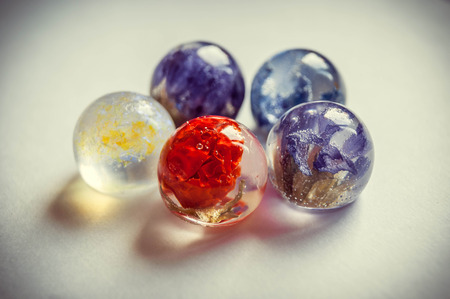 epoxy: Small dried Limonium, Solanum, Harebells and glitters inside frusto ball shaped crystal made of epoxy resin close-up  vintage toned