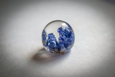 blue ball: Small dried harebell inside frusto ball shaped crystal made of epoxy resin close-up soft blue vintage toned