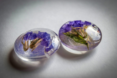 epoxy: Soft blue vintage toned dried flowers Limonium in two crystal made of epoxy resin close-up Stock Photo