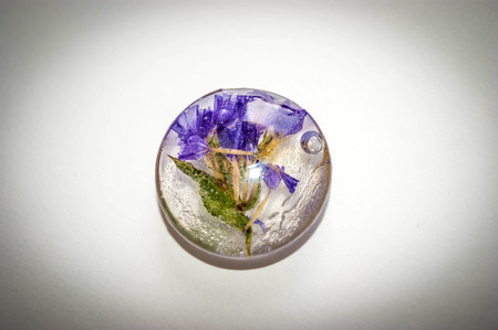 epoxy: Soft blue vintage toned dried flowers Limonium  in a crystal made of epoxy resin close-up Stock Photo