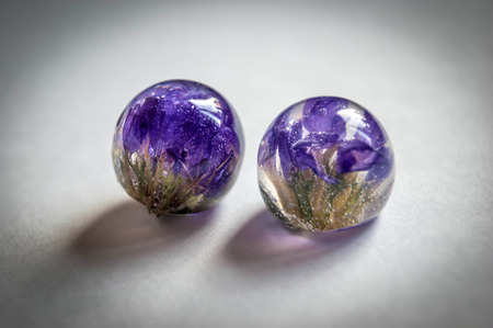 epoxy: Small dried Limonium inside two frusto ball shaped crystals made of epoxy resin close-up soft blue vintage toned