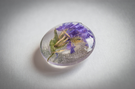 epoxy: Soft blue vintage toned dried flowers Limonium in a crystal made of epoxy resin close-up