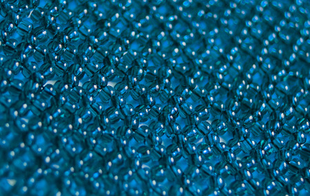 beaded: texture of blue beads in  woven beaded mesh close-up