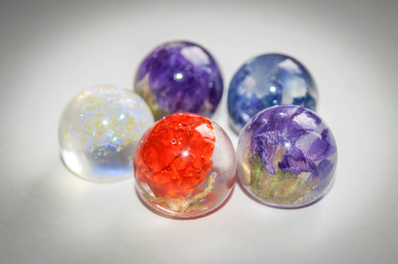 epoxy: Small dried Limonium, Solanum, Harebells and glitters inside frusto ball shaped crystal made of epoxy resin close-up soft vintage toned