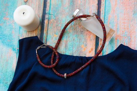 satin dress: Necklace and bracelet of the brown-red harness, made of beads and jewelry grid lies on a blue satin dress on the backdrop of blue old wooden surface and white perfume bottle lies and white candle stands near Stock Photo