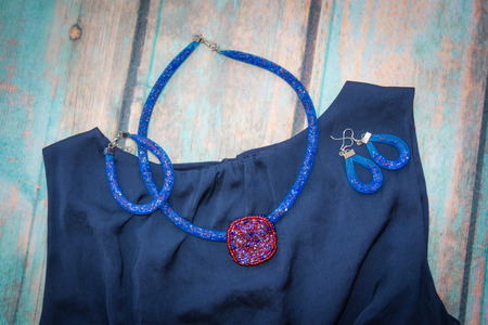 satin dress: Necklace with red beaded pendant, bracelet and earrings of the blue harnesses, made of beads and jewelry grid lies on a blue satin dress on the backdrop of blue old wooden surface Stock Photo