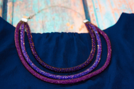 satin dress: Necklace of the three purple, blue and brown harnesses, made of beads and jewelry grid lies on a blue satin dress on the backdrop of blue old wooden surface