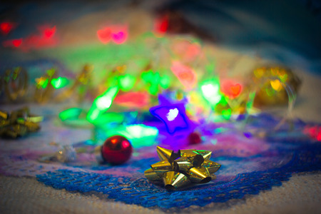 Gold bow and small red Christmas ball on a background of festive illuminations and decorations close-up toned image