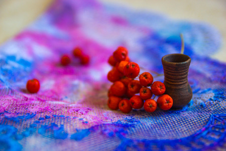 rowanberry: rowan berries and miniature pitcher on a background of blue and pink lace close-up Stock Photo