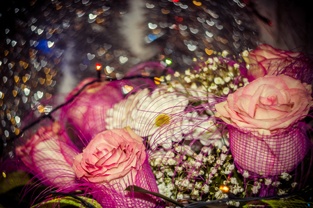 pink roses daisies and gypsophila with tinsel and bokeh on the background shallow depth of field Stock Photo