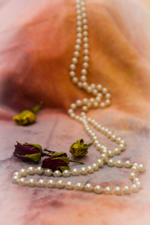 Dry red and yellow small roses buds and white pearl beads on orange fabric shallow depth of field