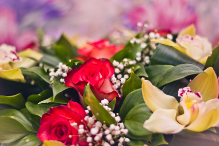Toned picture of Roses and Alstroemeria in a lush bouquet close-up shallow depth of field on purple background with white vignette Stock Photo