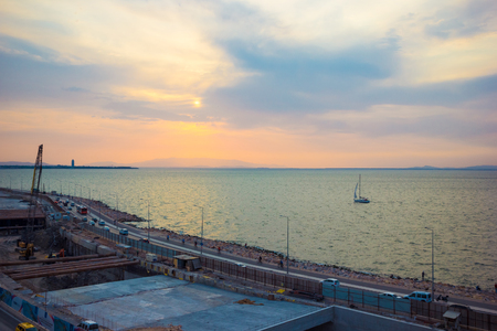 passerby: IZMIR, TURKEY – AUGUST  3, 2017: The process of building an underground tunnel on the road on the Aegean Sea in the Konak area of Izmir Turkey the view during sunset with a yacht floating on the sea toned image