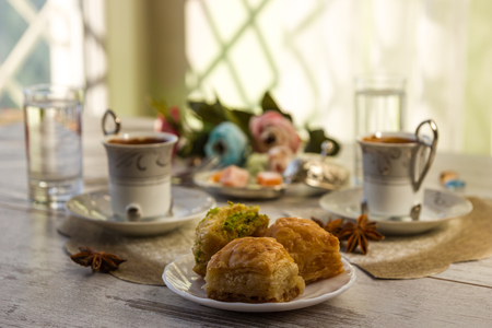Two cups of Turkish coffee and glasses of water and a plate with baklava lukum in lukumluk decorative flowers and badyan on a sunny day on a wooden table vintage toned picture close-up shallow depth of field