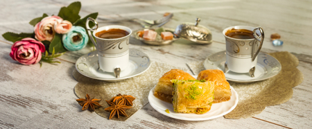 Two cups of Turkish coffee and glasses of water and a plate with baklava lukum in lukumluk decorative flowers and badyan on a sunny day on a wooden table vintage toned picture close-up shallow depth of field Stock Photo