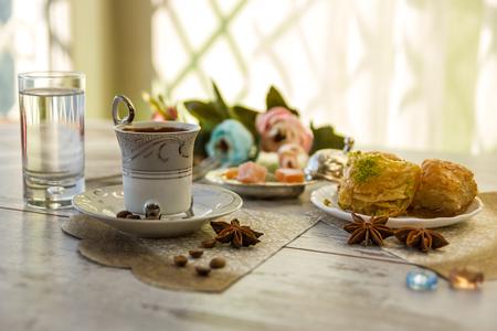 Taza de café turco y vasos de agua y un plato con baklava lukum en lukumluk flores decorativas y badyan en un día soleado en un cuadro de madera imagen vintage tonos baja profundidad de campo Close-up of field Foto de archivo - 86387751