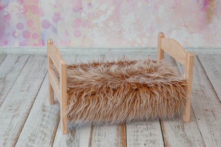 small wooden bed with faux fur blanket on pink background