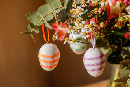 lush bouquet with berries and daisies and Easter eggs in sequins hang on it in sunlight close-up shallow depth of field