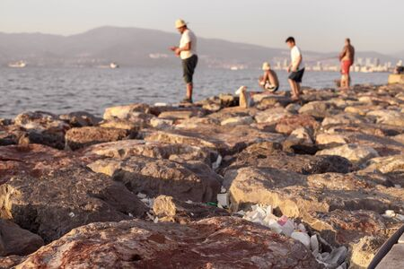 A lot of plastic trash in stones on sea coast. Concept of combating environmental problems pollution. On background are blurred fishermens. Sunset time, close-up, shallow depth of field