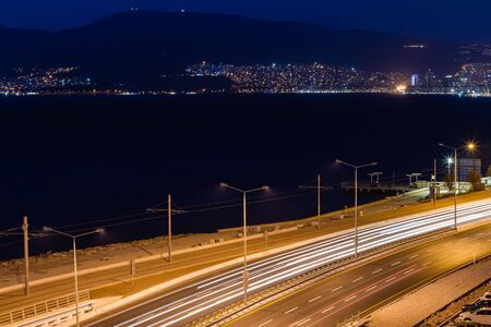 Evening view over the bay in Izmir, ship, mountains and tram rails. City Lights, Long Exposure